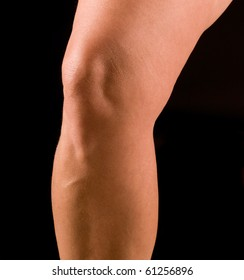 Study of athletic woman's knee, isolated on black