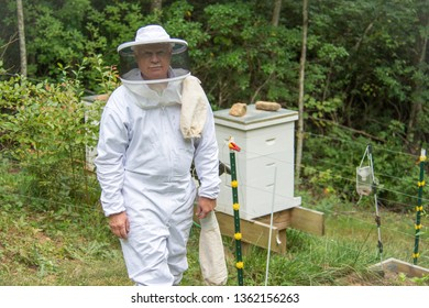 The study of bees, which includes the study of honey bees, is known as melittology. This Beekeeper is checking on the bee hives while wearing protective clothing in an attempt to not be stung.