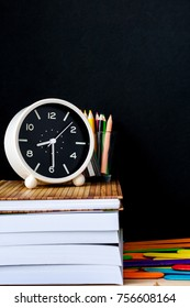 Study concept, Showing Clock, colour pencil and sticky note over the black background.