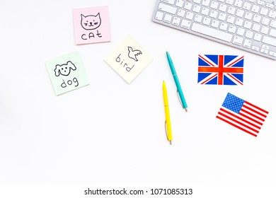 Study english online.English for kids. Elementary. British and american flags, computer keyboard, stickers with vocabulary on white background top view copy space