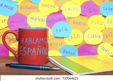 Study French concept, a mug with written words Speak Spanish, notebook, pen and notes with common spanish words.