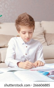 Study hard. Vertical shot of a small cute schoolboy doing writing in his exercise book at home