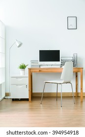 Study room with wood flooring and simple, light furniture