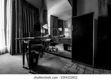 Study room with writing desk armchair lamp and mirror