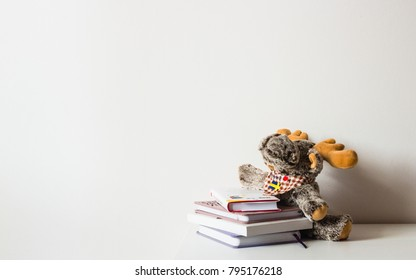 Study in Sweden concept. Studying abroad, international education. Toy moose with Swedish flag hugs books, isolated on white background