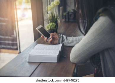 Study and technology concept.Sad woman (christian) hands on bible at coffee shop,send message by mobile phone.People side view,hold smartphone.Asian student reading books and study for exam in library