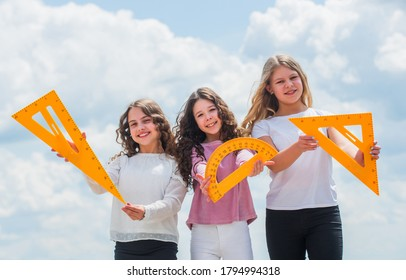 Study together. Clever kids. Study group can help solidify and clarify material. Education concept. School students learning geometry. Girls with triangle ruler. Smart friends. School friendship.
