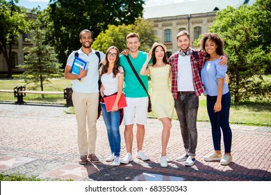 Study together is fun, teamwork,teambuilding concept. Six happy students are standing near university building and holding books, wearing casual smart, smiling and embracing on a sunny spring day