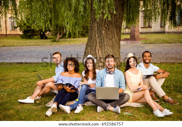 Study together is fun, teamwork,teambuilding concept. Six happy students are sitting under the tree near college building and holding books, devices, wearing casual smart, smiling, on  nice summer day