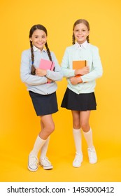 Studying english literature. Little girls holding books of language and literature on yellow background. Small children enjoying childrens literature. Having literature lessons at school.