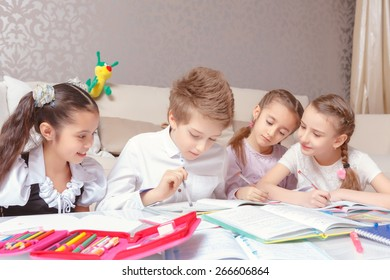 Studying in group. Three cute junior school girls and a boy doing tasks together sitting by the table at home