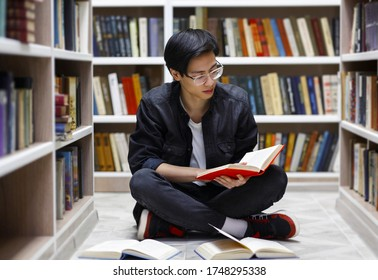 Studying Hard. Focused asian male student sitting on the floor at campus library, reading a book, copy space