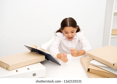 Studying hard. Girl child reads book while sit table white background. Schoolgirl studying and reading book. Kid school uniform angry irritated difficult task. Pupil emotional irritated expression.