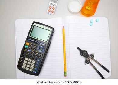 Studying into Oblivion/Calculator, pencil, pills, compass arrayed over collegiate notebook