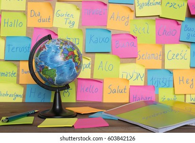 Studying languages concept, a globe and color notes with the word Hello in different languages.