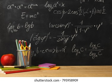 Studying mathematics educational background. Pencils, scissors and apple against classroom blackboard with chalk writing of sums. Back to school, research concept