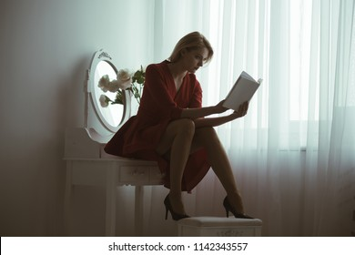 studying poetry. sexy woman studying poetry sitting in bedroom. studying poetry at home. girl in red dress studying poetry. passionate reader