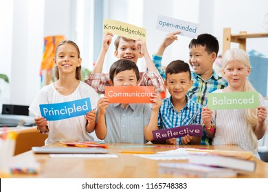 Studying time. Smiling joyful schooldchildren standing in the middle of a classroom while holding tables in their hands
