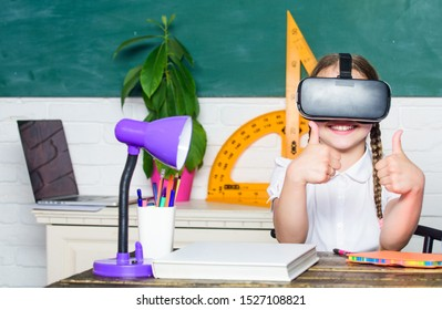 Studying in virtual reality. Modern technology. Interesting lesson. Homeschooling online. Girl kid study in virtual school. Virtual education. Child cute pupil wear hmd vr glasses. Virtual teaching.