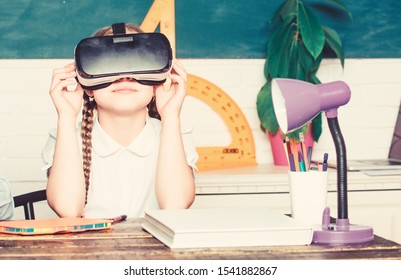 Studying in virtual reality. Modern technology. Interesting lesson. Virtual teaching. Homeschooling online. Girl kid study in virtual school. Virtual education. Child cute pupil wear hmd vr glasses.