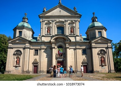 STUDZIANNA, POLAND - JULY 07, 2015: Tourists admire the Basilica of Saints Philip Neri and John the Baptist