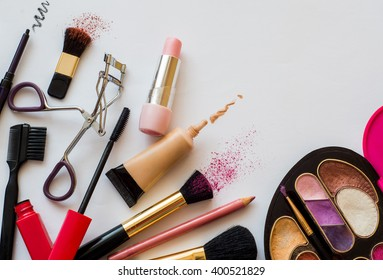 stuff from the female cosmetic bags. cosmetics and makeup brushes on a white background