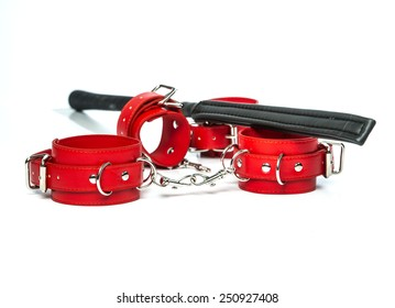 Stuff for sexual role playing: black whip or flogger made of black leather and red hand cuffs.