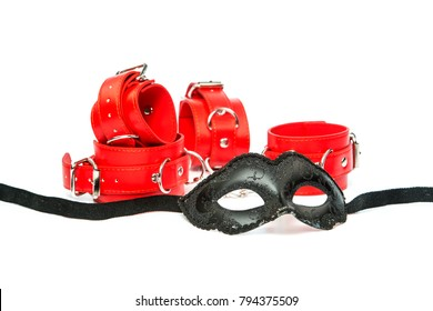 Stuff for sexual role playing: fetish mask in venetian style togehter with red hand cuffs.