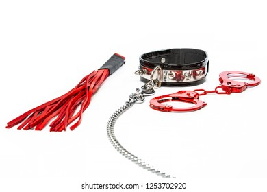 Stuff for sexual role playing: red hand cuffs togehter with a collar made of black leather and a steel chain and  a flogger or whip made of red leather.