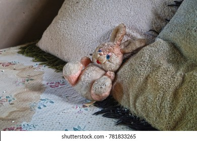 Stuffed animal (rabbit) on bed in an abandoned and neglected house. Natural light.