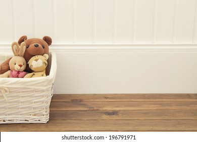 Stuffed animal toys in a basket on the floor. A white wainscot.