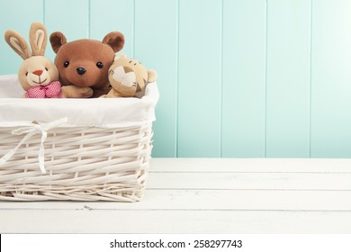 Stuffed animal toys in a basket on the floor. A turquoise wainscot.