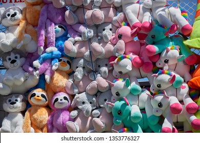 Stuffed animal toys at a fair as prizes hanging on mass on a wall.