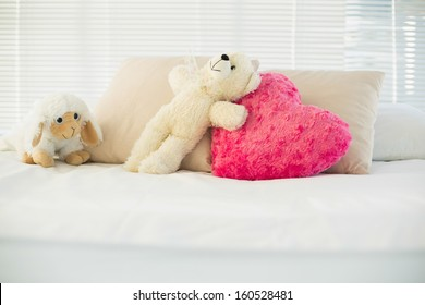 Stuffed animals and a heart pillow lying on couch in living room