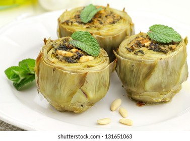 Stuffed artichokes on a plate with fresh mint and pine nuts