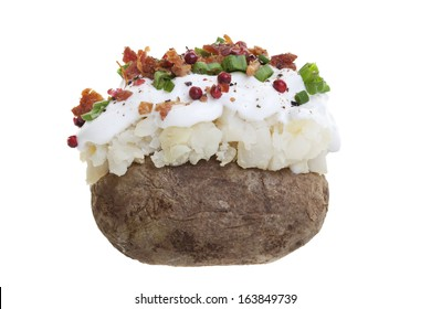 A stuffed baked potato with sour cream, bacon bits, and Green onions. Shot on a white background.