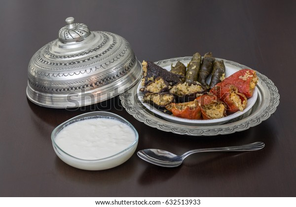Stuffed bell peppers, eggplant, and grape leaves with yoghurt and spoon