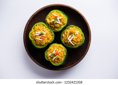 Stuffed  capsicum or bharwa shimla mirchi is a popular Indian main course recipe. Served in a plate over moody background. Selective focus
