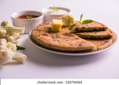 Stuffed cauliflower / Gobi Paratha is a Indian flatbread. favourite breakfast or lunch menu in north India, served over moody background with curd and tomato ketchup in bowl. selective focus