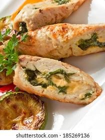 Stuffed chicken fillet with spinach and cheese, served with grilled vegetables and fresh parsley on white plate