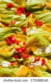 Stuffed courgette flowers with ricotta cheese, baked in oven with tomatoes top view, closed up composition