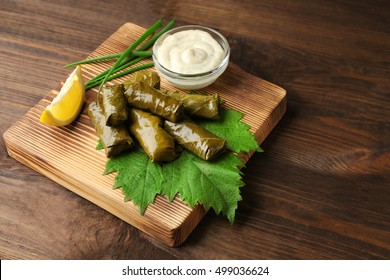 Stuffed delicious Dolma with sauce and lemon on wooden board