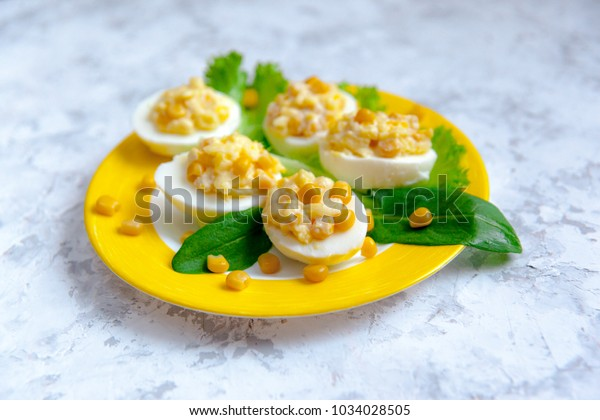 Stuffed eggs with cheese and corn on a yellow plate