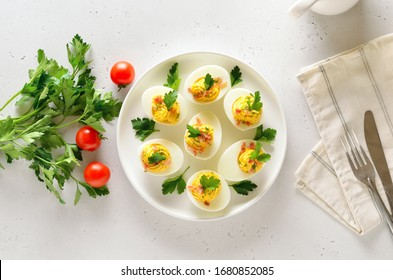 Stuffed eggs with egg yolk, bacon, mustard and parsley. Healthy diet food for breakfast. Top view, flat lay.