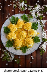 Stuffed eggs. Mimosa egg salad on rustic wooden board top view. Blossoming tree branches. Easter dishes.
