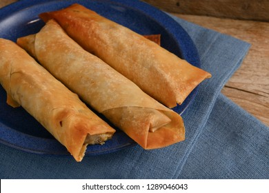 stuffed filo or yufka dough rolls with a spicy meat filling on a blue plate on a rustic wood, selected focus, narrow depth of field