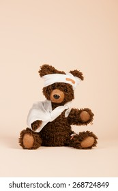 Stuffed hand made bear with pain and plaster sitting on beige background
