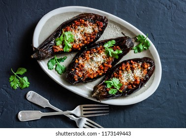 Stuffed lentils roasted eggplant - delicious healthy vegetarian lunch, snack, appetizer on a dark background, top view