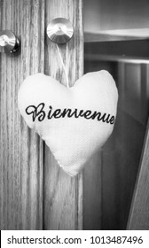 A stuffed material heart with the word bienvenue (French for welcome) embroidered on it in black and white