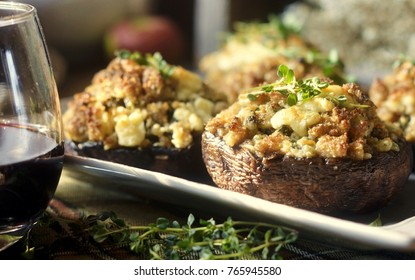 Stuffed mushrooms with Italian sausage, breadcrumbs, fresh sage, thyme, and melted blue cheese; with a glass of red wine.  Selective focus.